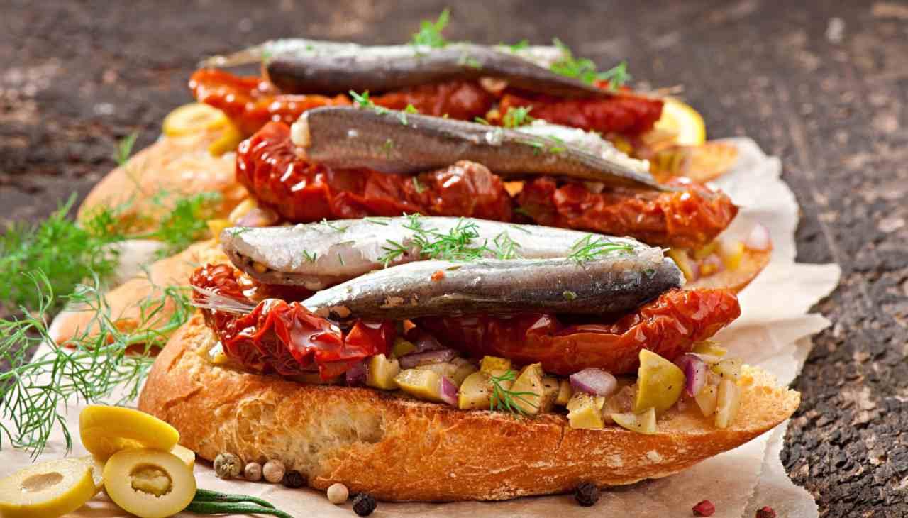 Finger food di pane tostato con pesce e pomodori secchi
