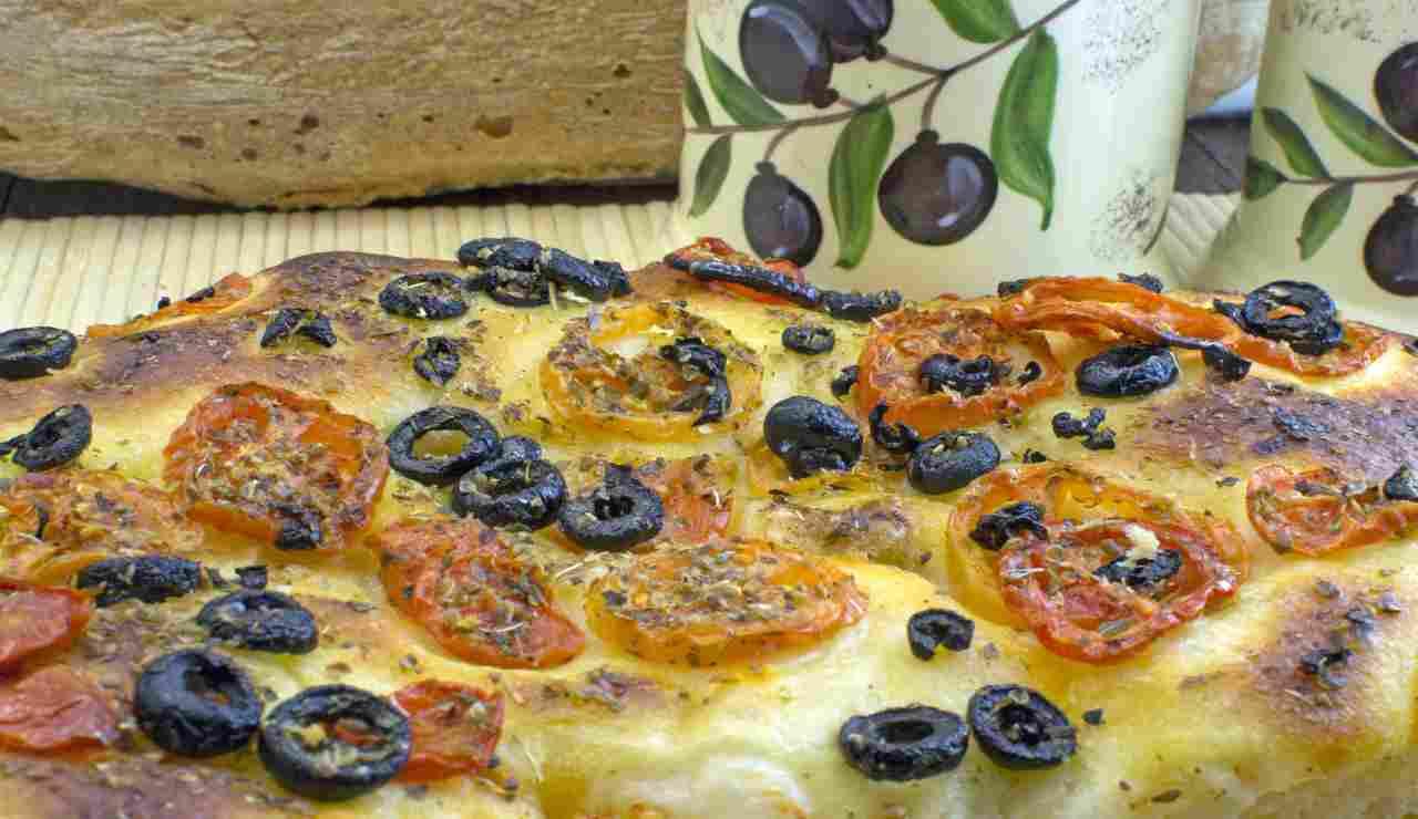 Focaccia morbida e alta con pomodorini origano e olive AdobeStock