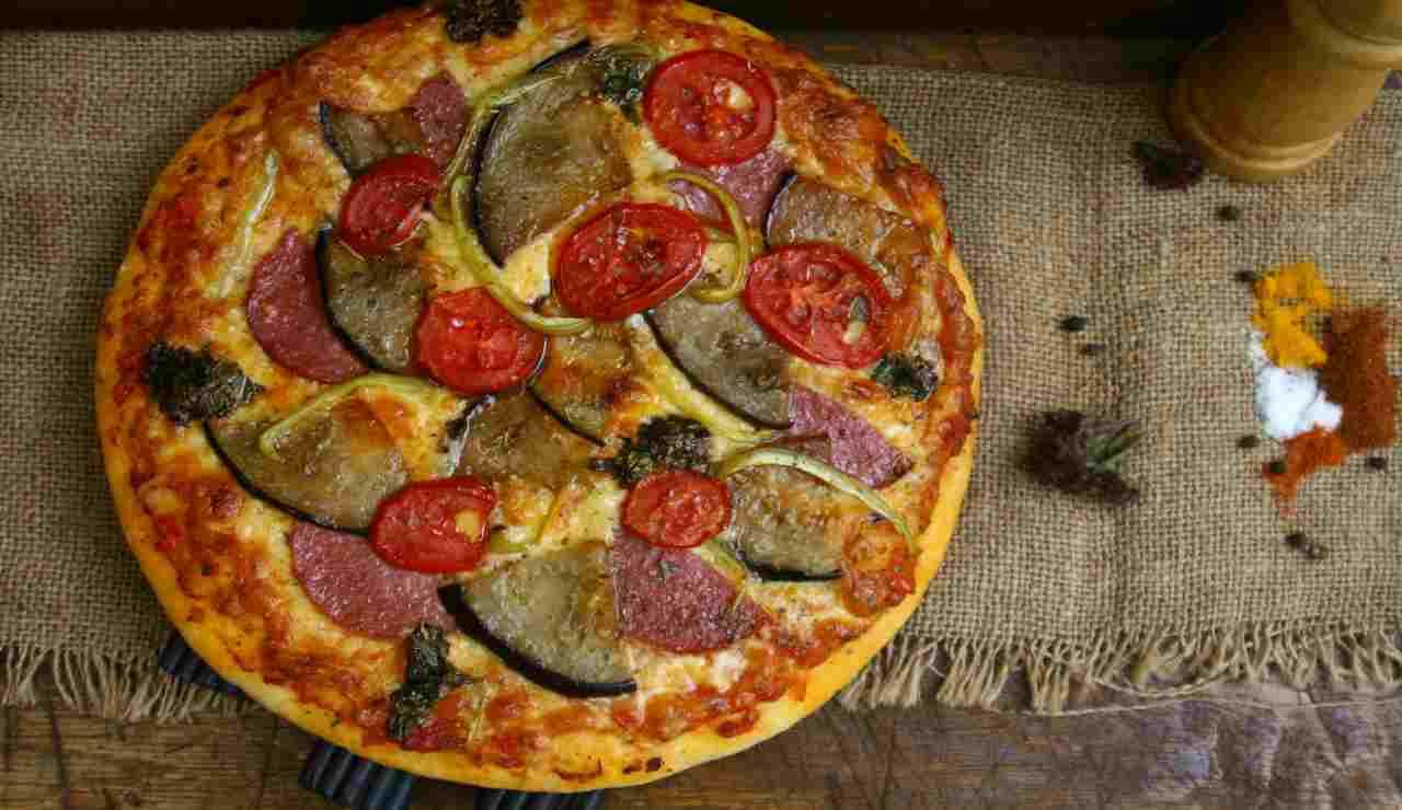 Pizza sprint con salame melanzane e pomodori AdobeStock (1)
